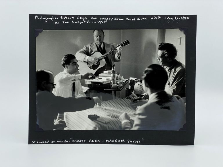 Photograph of Robert Capa and Burl Ives visiting John Huston in the hospital, 1953. Ernst HAAS.